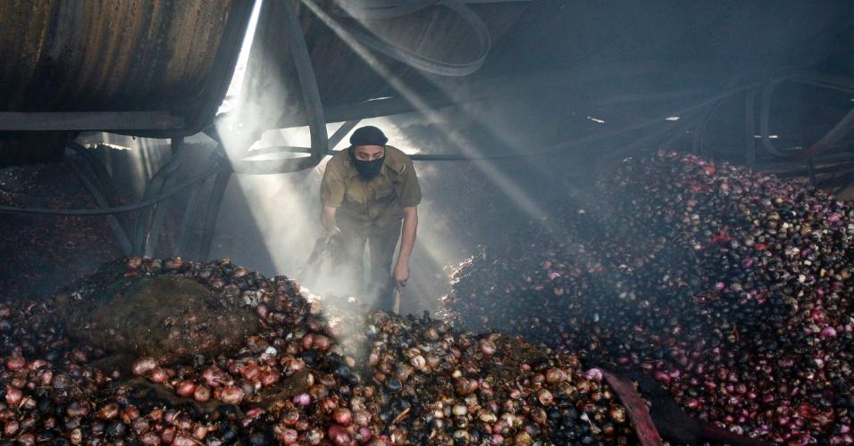 9.mai.2012 - Bombeiro esvazia sacos de cebolas queimadas após incêndio que atingiu mercado em Jammu, na Caxemira