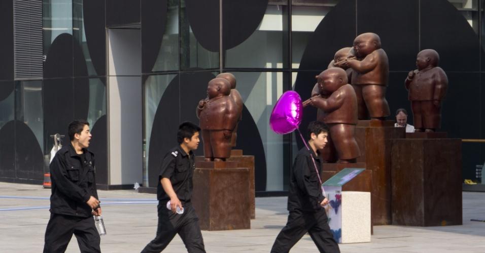9.mai.2012 - Guardas caminham em meio a grupo de esculturas em bronze do artista chinês Qu Guangci exibidas em centro comercial de Pequim, na China
