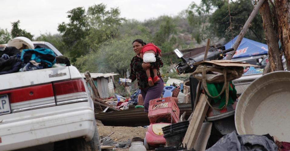 9.mai.2012 - Mulher com bebê no colo caminha entre os escombros de um tornado que atingiu La Providencia, no Estado de Nuevo Leon, no México