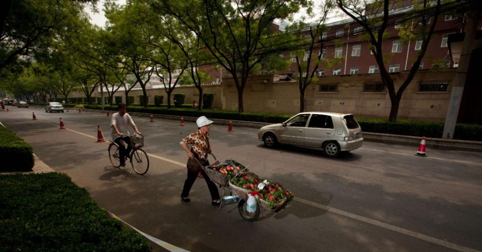 9.mai.2012 - Mulher empurra carrinho de frutas em frente ao hospital Chaoyang, onde o ativista cego chinês Chen Guangcheng recebe tratamento em Pequim, na China