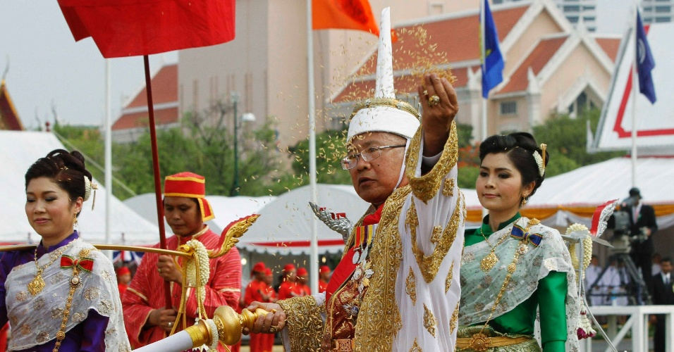9.mai.2012 - Oficial usando vestes tradicionais lança grãos de arroz em Bancoc, na Tailândia, cerimônia anual que marca o fim da estação seca e celebra o início da temporada de plantações