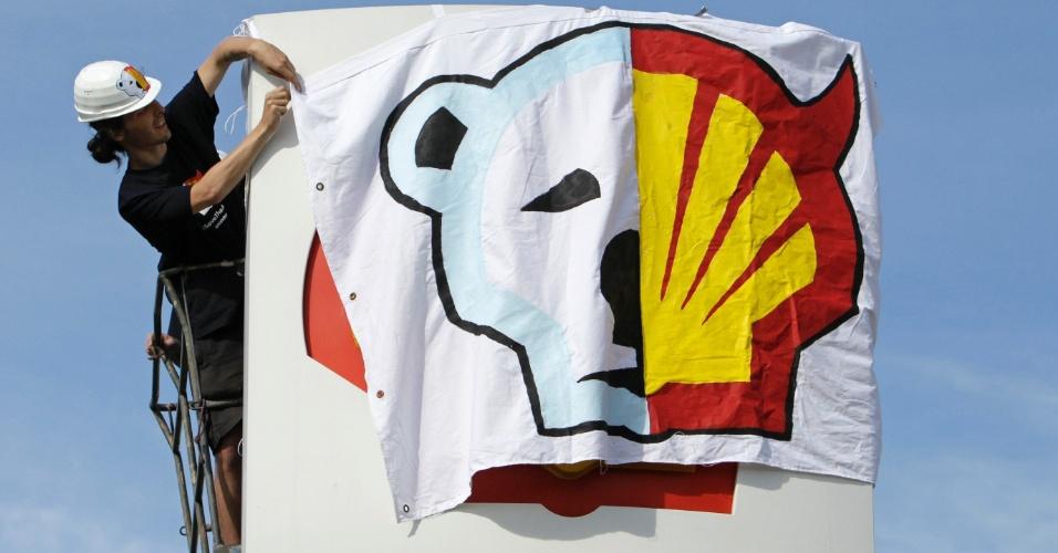 10.mai.2012 - Ativistas do Greenpeace penduram uma bandeira em uma estação de petróleo da Shell, em Praga, na República Tcheca
