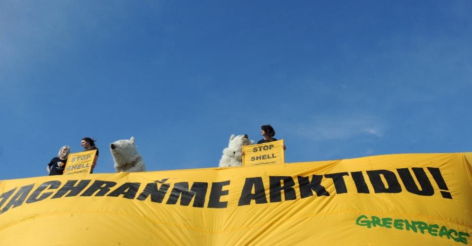 10.mai.2012 - Ativistas do Greenpeace vestem roupa de urso polar e seguram uma faixa escrito