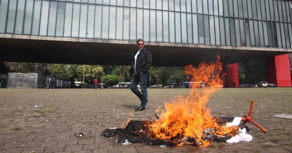 10.mai.2012 - Homem ateia fogo às roupas dele da marca Zara no vão do Mascp, em São Paulo, em protesto contra o trabalho escravo envolvido na produção das roupas da loja