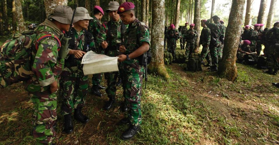 Soldados da Marinha indonésia marinhos utilizam mapas para estudar o local onde foram localizados os destroços do avião russo Sukhoi