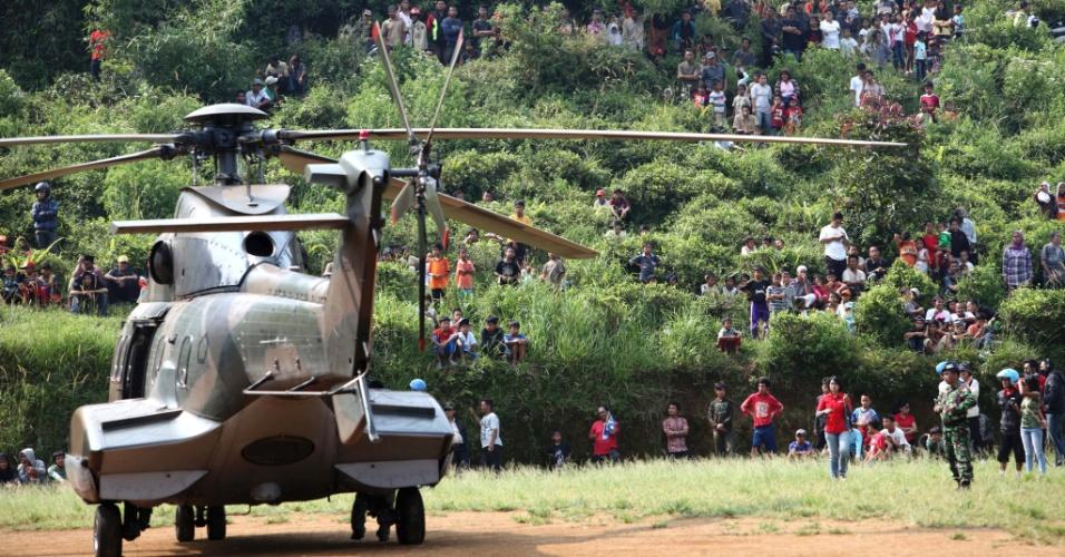 11.mai.2012 - Indonésios observam decolagem de helicóptero de resgate que seguiu para a área onde se concentram os destroços do avião russo que caiu e matou as 45 pessoas a bordo