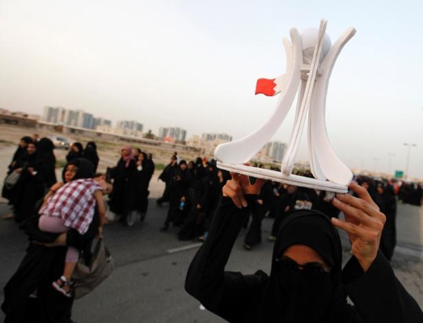 11.mai,2012 - Manifestantes contrários ao governo bareinita seguram miniatura do monumento que ficava na praça Pérola, durante protesto na vila de Karzakan, ao sul de Manama, no Bahrein