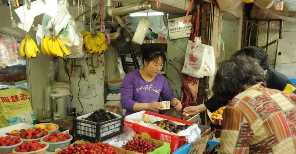 11.mai.2012 - Mulher vende frutas em barraca em Xangai, na China