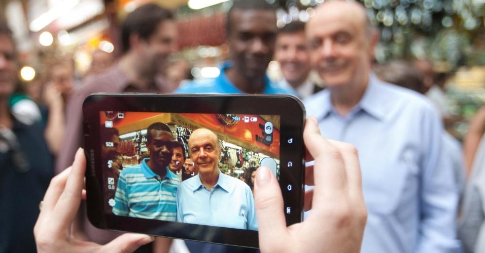 11.mai.2012 - Pré-candidato do PSDB à prefeitura de São Paulo Jose Serra tira foto com um possível eleitor durante visita ao Mercado Municipal