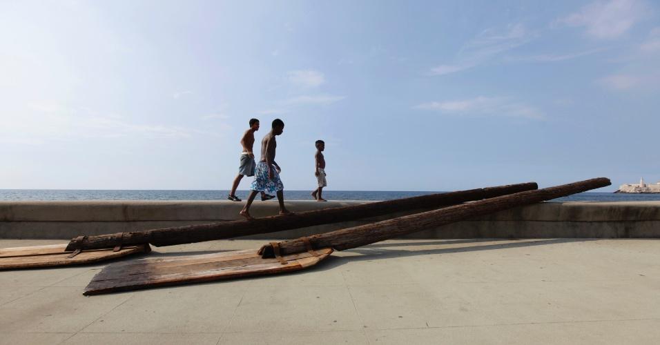 """11.mai.2012 - Rapazes caminham em avenida à beira-mar """"El Malecon"""", em Havana, em Cuba, e passam pela obra do artista cubano Alexis Leyva Machado"""