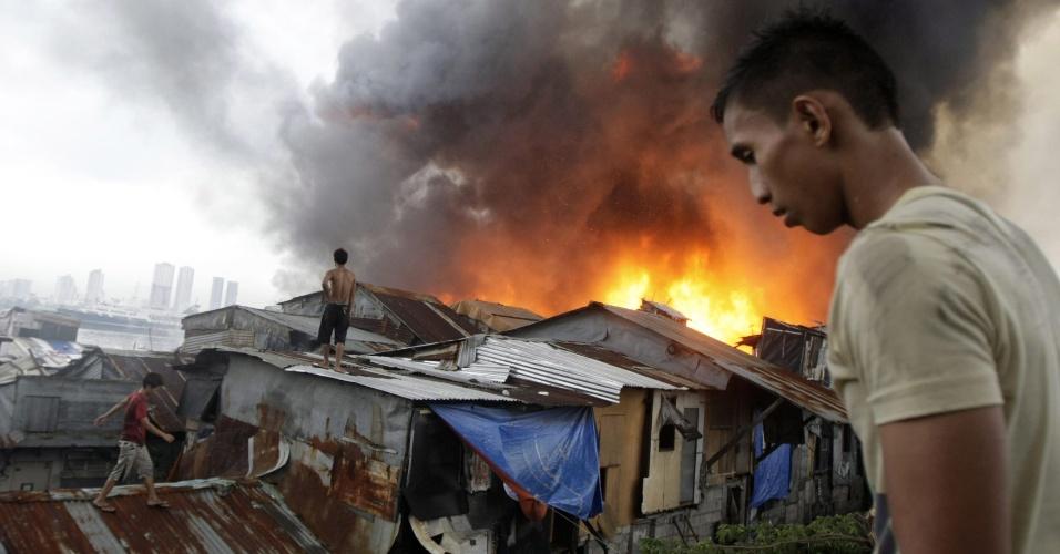 11.mai.2012 - Rapazes observam, nesta sexta-feira (11), incêndio em favela de Manila, nas Filipinas. O fogo deixou cerca de 5.000 pessoas sem suas casas e continua sem controle, segundo a agência EFE