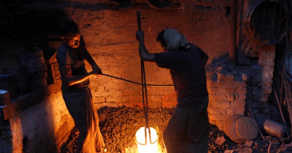 11.mai.2012 - Trabalhadores manipulam aço líquido em fábrica de máquinas têxteis em Ahmedabad, na Índia