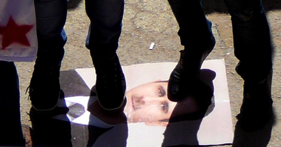 11.mai.2012 ¿ Manifestantes pisam em cartaz com o rosto do ditador Bashar al Assad durante manifestação contra o regime sírio, em Deraa