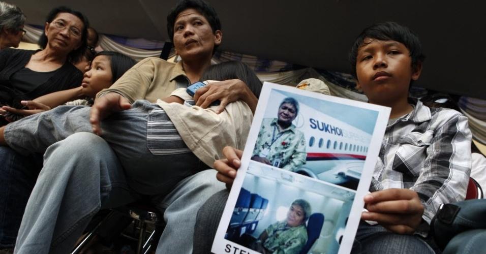 12.mai.2012 - Bima Kamagi, 14, aguarda ao lado de sua mãe e de sua irmã mais nova a identificação do corpo de seu pai, Steven Kamagi, um dos passageiros do avião russo que caiu na Indonésia na quarta-feira (9)