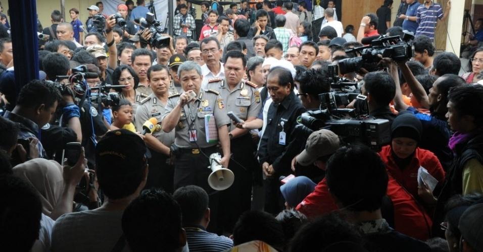 12.mai.2012 - Oficial da polícia indonésia fala com parentes das vítimas do avião russo que caiu próximo à capital Jacarta