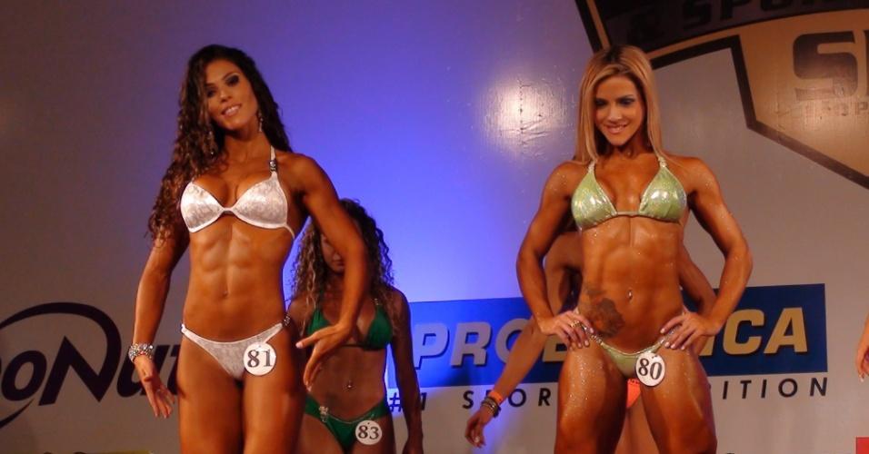 Belas mulheres mostram o corpo definido pela musculação em campeonato de fisiculturismo