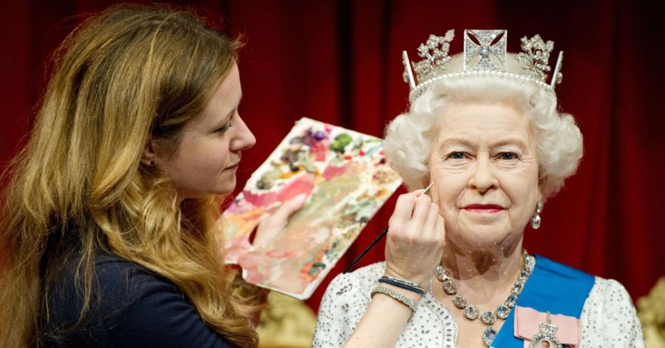 A pintora Lisa Burton retoca estátua de cera da Rainha Elizabeth 2ª, no Madame Tussauds, em Londres (14/5/12)