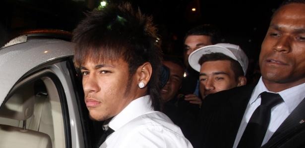 Neymar chega com segurança; ao fundo, de boné, jovem que se envolveu em confusão