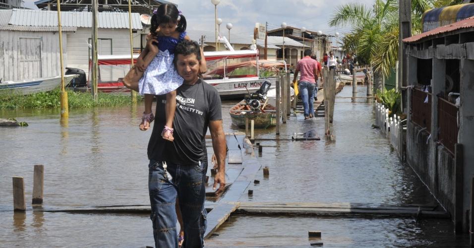15.mai.2012 - Morador recorre à passarela improvisada para passar pelas ruas do município do Careiro da Várzea (AM), castigado pelas cheias dos principais rios do Estado