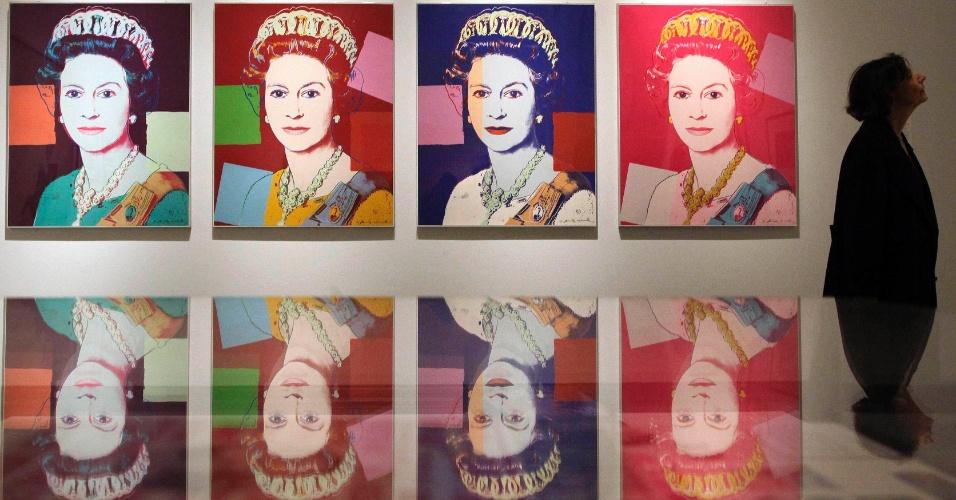16.mai.2012 - Visitante da National Portrait Gallery, em Londres, observa obras da pinacoteca, ao lado de serigrafias do artista americano Andy Warhol que retratam a rainha Elizabeth 2ª