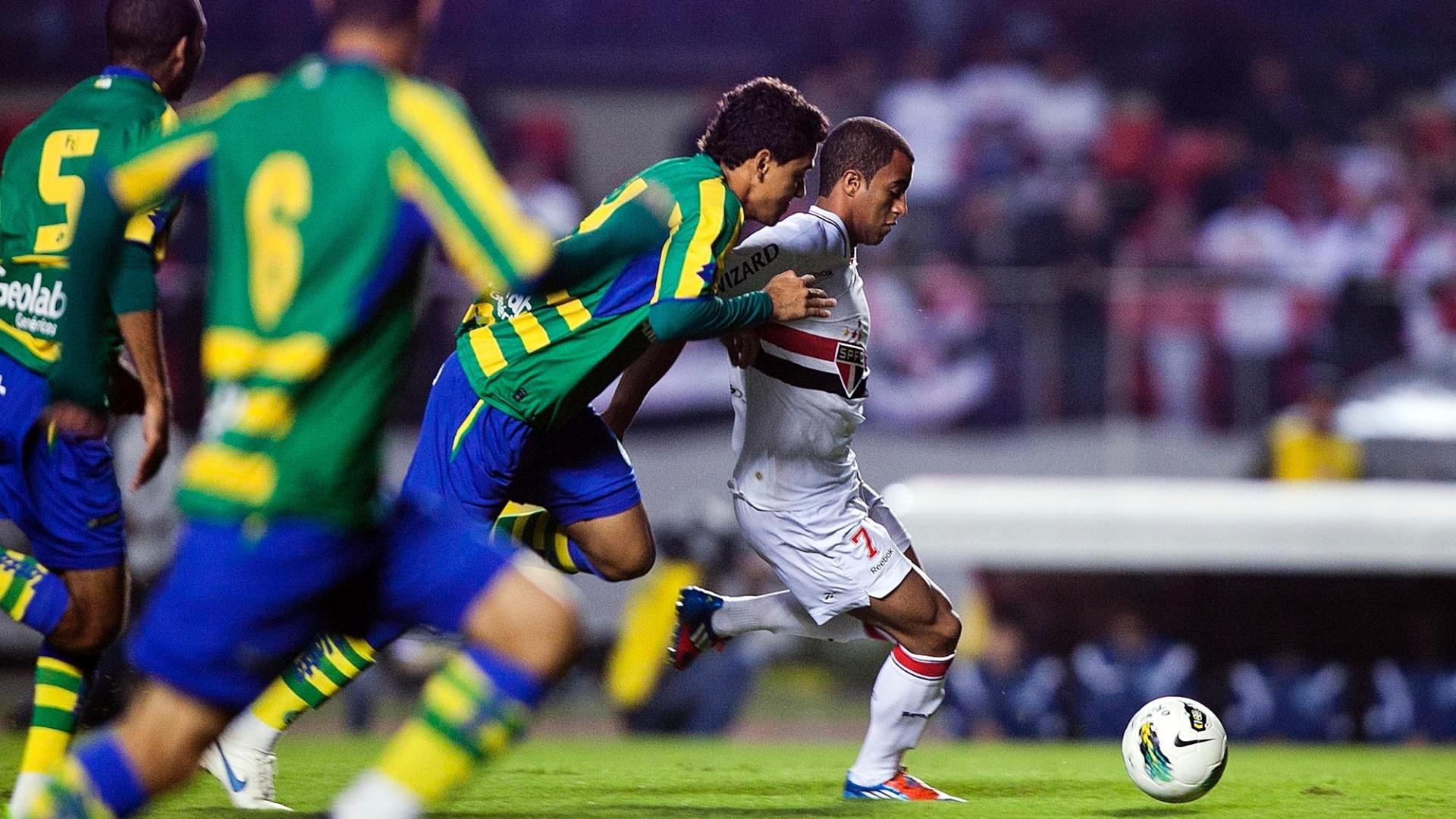 Lucas, meia do São Paulo, conduz a bola cercado por três jogadores do Goiás no primeiro lance da partida realizada no Morumbi