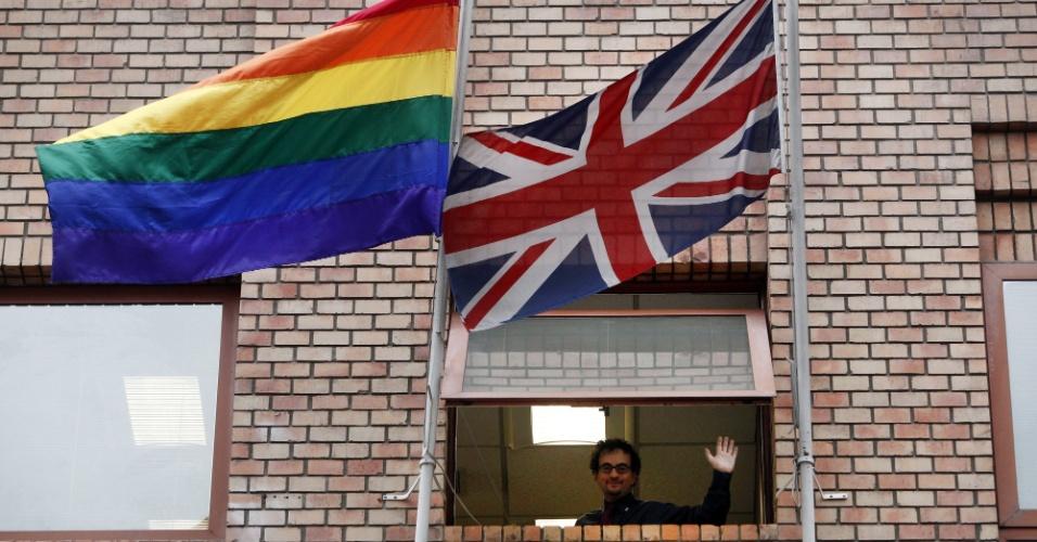 17.mai.2012 - Embaixador do Reino Unido no Chile, Jon Benjamin, acena após colocar a bandeira gay ao lado da britânica, na sede da embaixada, em apoio ao Dia Internacional Contra a Homofobia