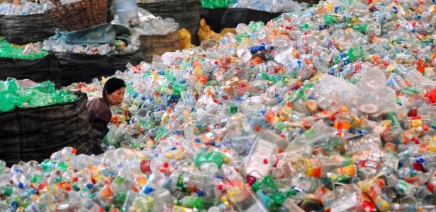 Trabalhadora caminha entre embalagens plásticas em centro de reciclagem em Jiangsu, na China