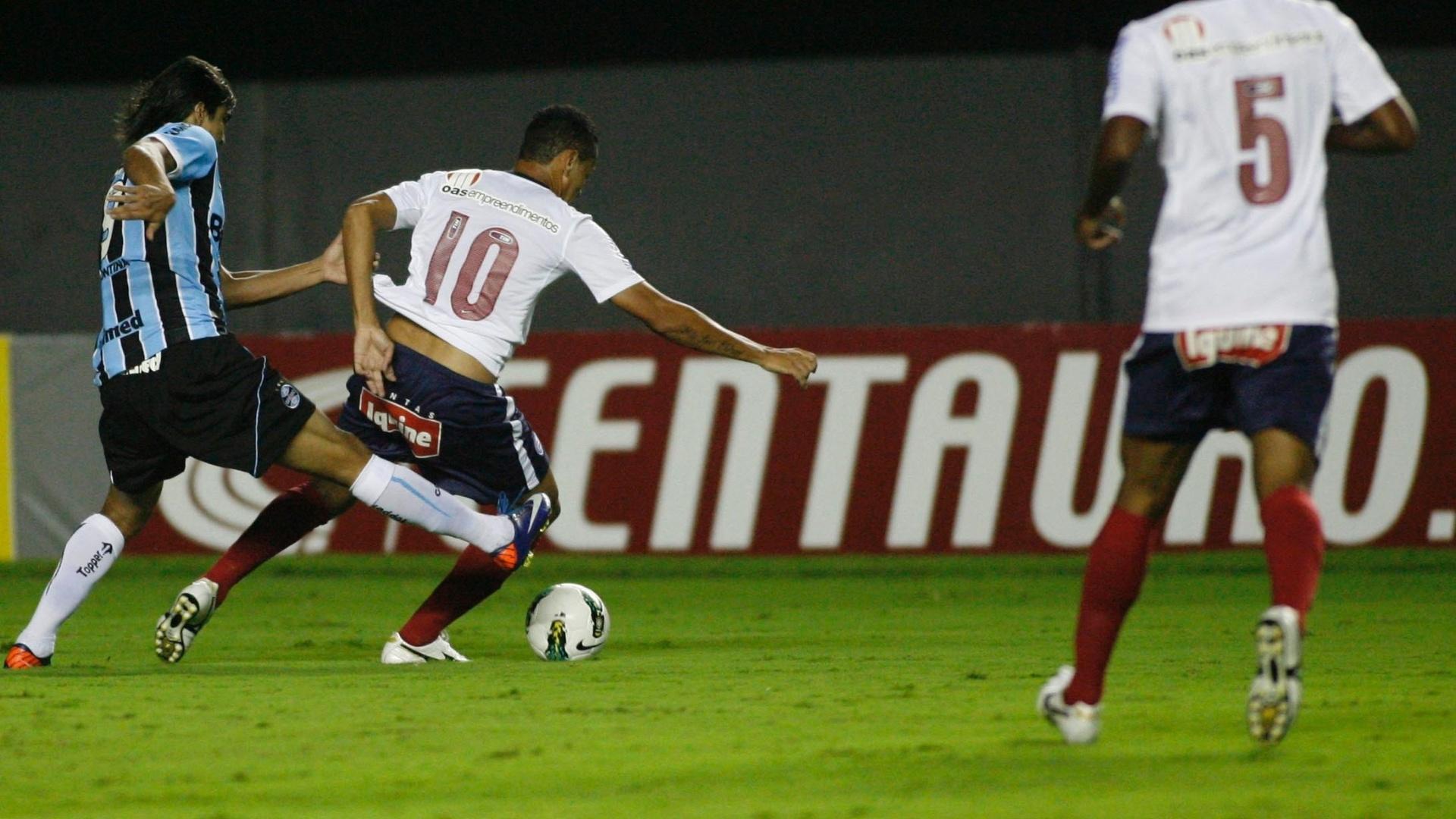 Hélder, meia do Bahia, protege a bola da chegada de Marcelo Moreno, do Grêmio