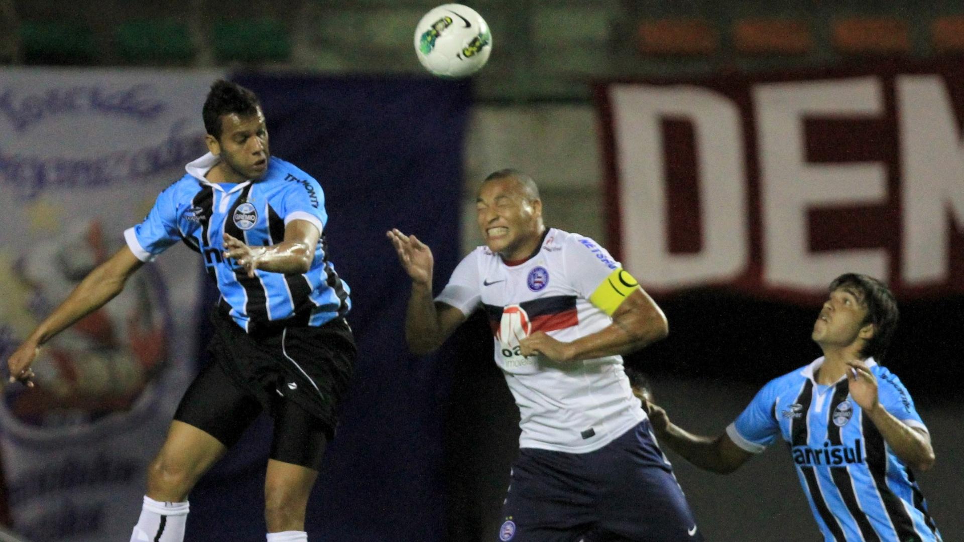 Titi, do Bahia, tenta alcançar a bola entre dois jogadores do Grêmio