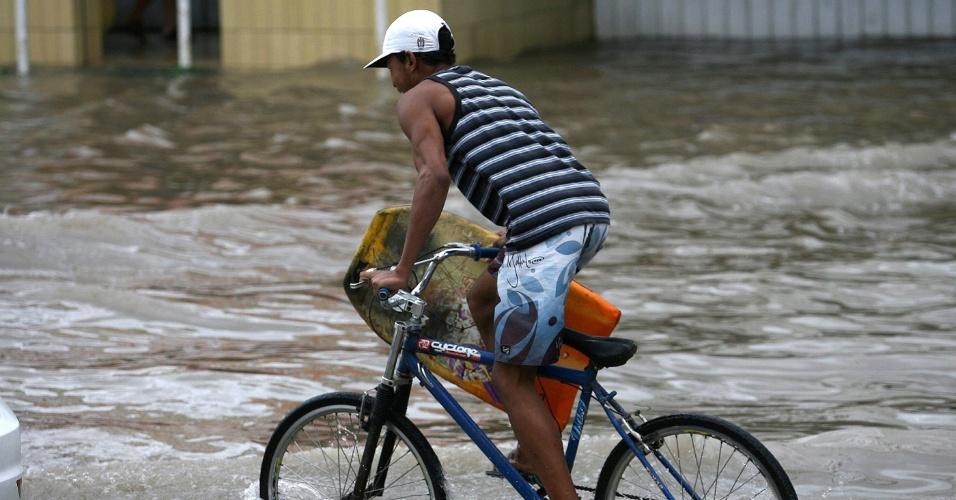18.mai.2012 - Homem anda de bicicleta por rua alagada de Salvador, na Bahia, após forte chuva que atingiu a capital baiana