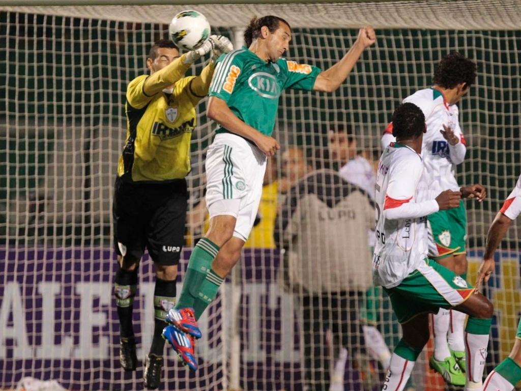 Atacante Barcos disputa pelo alto a bola com o goleiro Weverton na estreia de Palmeiras e Portuguesa no Brasileirão