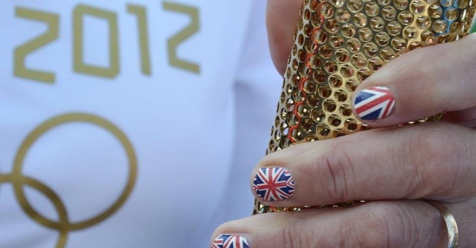 Sarah Blight segura a tocha olímpica, em Cornwall, no sudoeste da Inglaterra