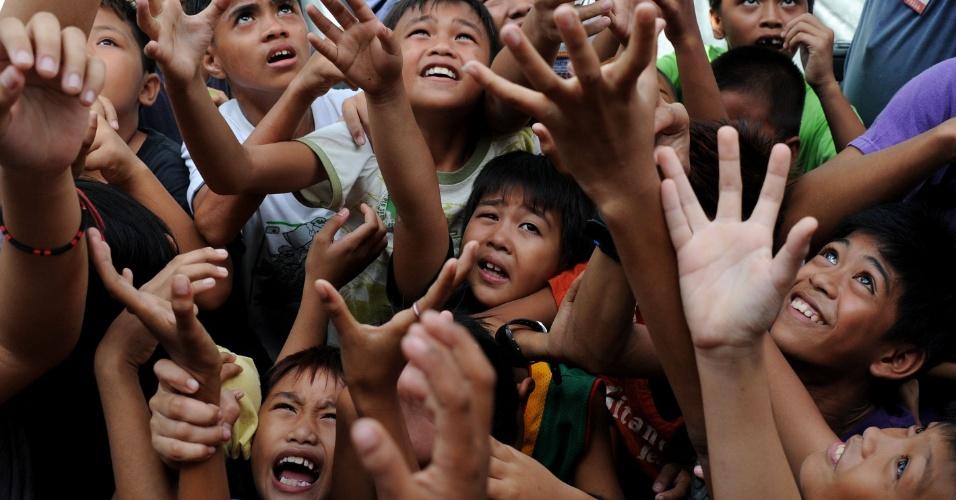 20.mai.2012 - Crianças pulam para pegar doces em brincadeira durante festival religioso em homenagem a Santa Rita de Cássia em Manila, nas Filipinas