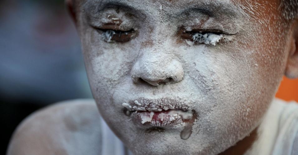 20.mai.2012 - Crianças usam canudos para assoprar farinha dentro de copos de plástico em brincadeira durante festival religioso em homenagem a Santa Rita de Cássia em Manila, nas Filipinas