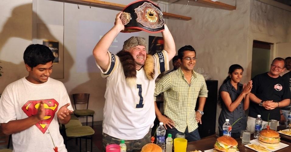 20.mai.2012 - Dale Boone levanta cinturão de campeão mundial de comilança na final asiática do concurso organizado pelo  WLOCE (Liga Mundial de Alimentação Competitiva) em Bangalore, na Índia, neste domingo (20). O americano comeu um hambúrguer de dois quilos em 18 minutos na competição