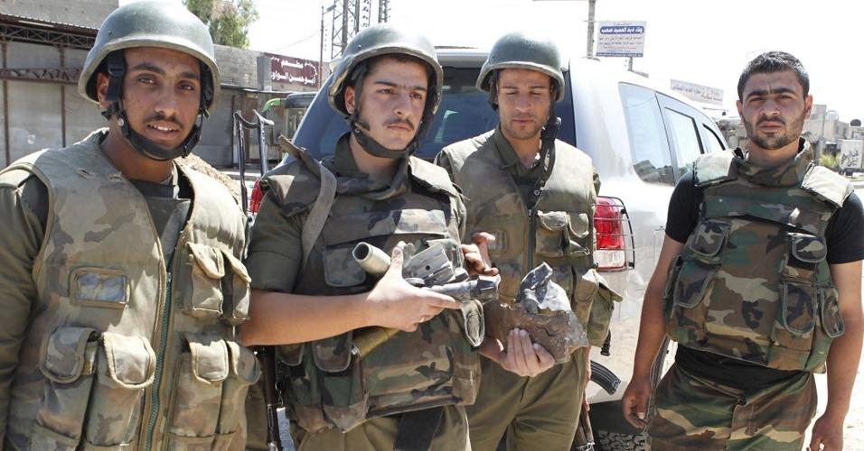 20.mai.2012 - Homem mostra projéteis disparados durante visita de observadores da ONU no bairro de Duma, próximo a Damasco, na Síria, neste domingo (20). Pelo menos dois civis ficaram feridos em uma explosão na cidade. O grupo da ONU saiu ileso do incidente