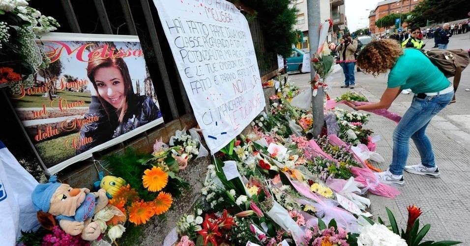 20.mai.2012 -  Jovem deposita flores em frente ao colégio Morvillo Falcone, neste domingo (20), em Brindisi, a leste da Itália, em que uma bomba explodiu no último sábado (19) e deixou estudantes mortos e feridos