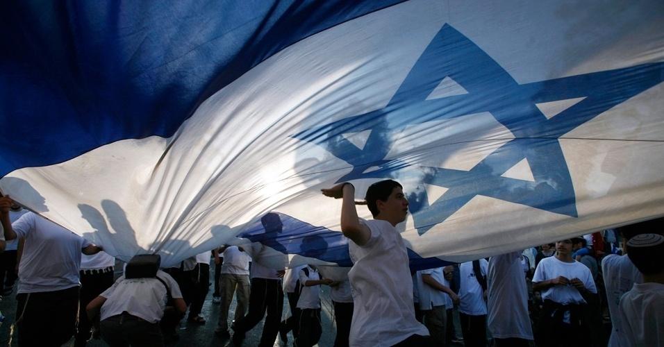 20.mai.2012 - Jovem israelense dança embaixo da bandeira nacional durante um desfile em comemoração ao Dia de Jerusalém, neste domingo (20). O feriado marca a libertação da cidade e sua reunificação após a Guerra dos Seis Dias