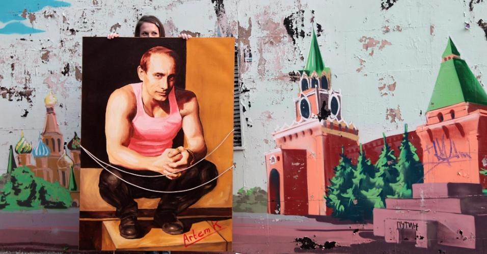 20.mai.2012 - Manifestante exibe pintura do presidente russo, Vladimir Putin, em protesto em Moscou, na Rússia