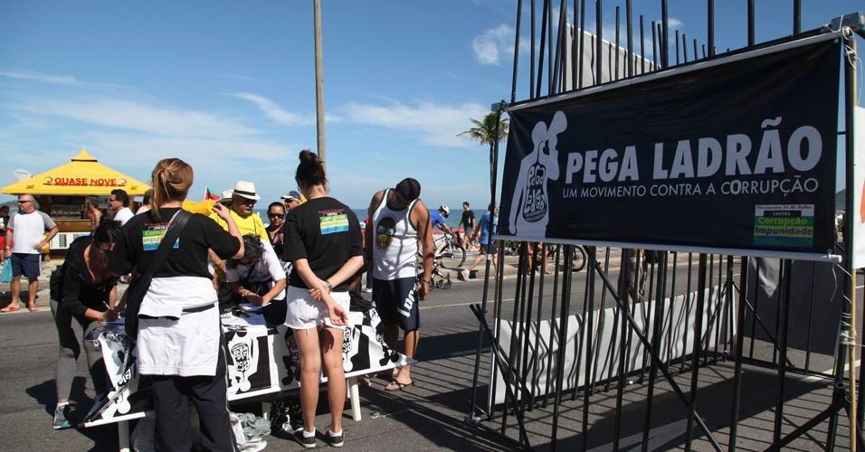 20.mai.2012 - Manifestantes montam cadeia simbólica na orla da praia de Ipanema, no Rio de Janeiro, neste domingo (20). A iniciativa chamou a atenção para a demora do Supremo Tribunal Federal (STF) em votar o processo do mensalão. No calçadão, foram colhidas cerca de 1,2 mil assinaturas em uma petição