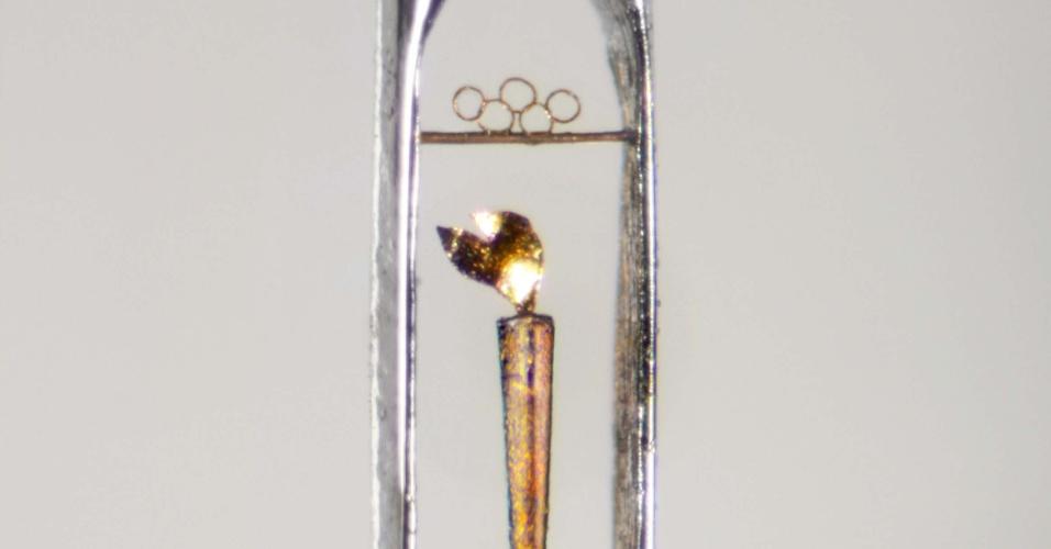 Mini tocha olímpica criada por artista britânico que cabe dentro de um buraco de agulha