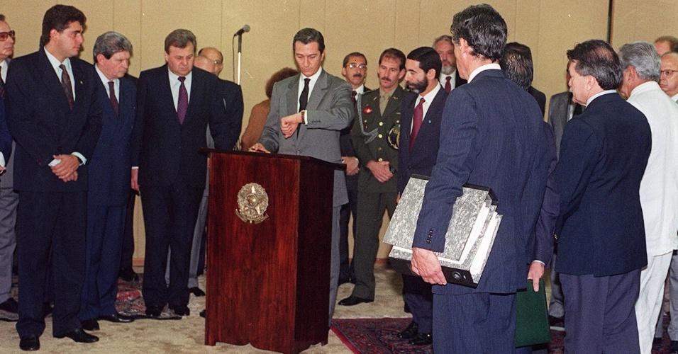 22.mai.2012 - Collor olha para o relógio momentos antes de assinar o documento pelo qual reconhece que responderá, fora do exercício do cargo, por crime de responsabilidade, em Brasília, em outubro de 1992
