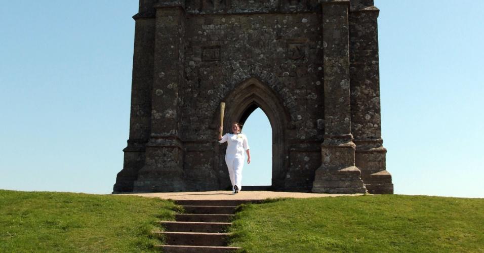 Carregadora ergue a tocha olímpica em frente das ruínas da Igreja de St. Michael.