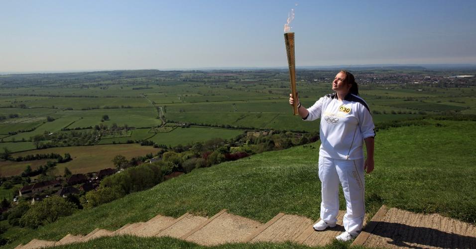 Carregadora ergue a tocha olímpica no alto da Glastonbury Tor. Ao fundo a cidade de Glastonbury, pequena cidade inglesa com menos de 10 mil habitantes