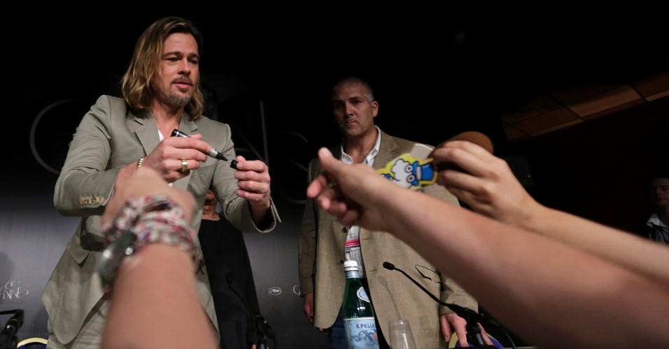 O ator Brad Pitt dá autógrafos durante conferência sobre o filme