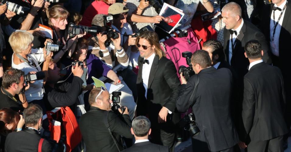 O ator Brad Pitt é cercado por fotógrafos ao chegar à exibição de