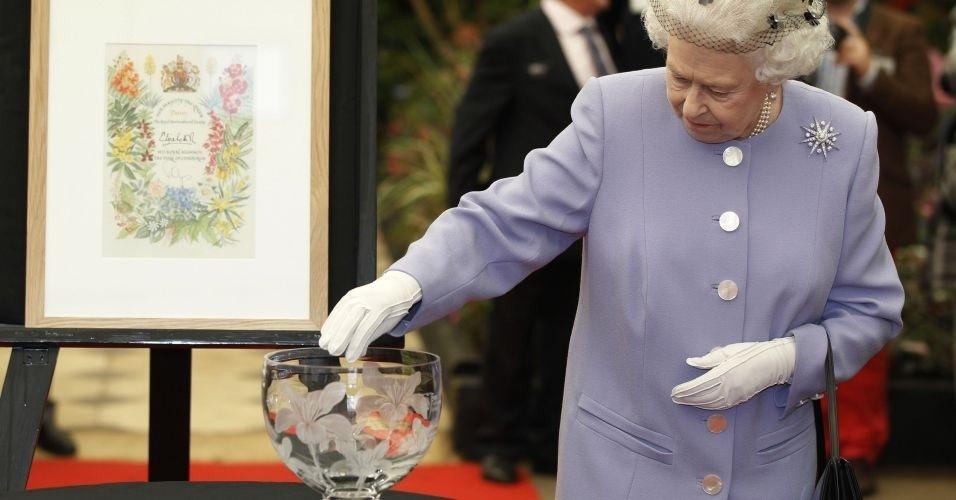 21.mai.2012 - Rainha Elizabeth 2ª examina vaso de vidro no durante visita ao Chelsea Flower Show, em Londres