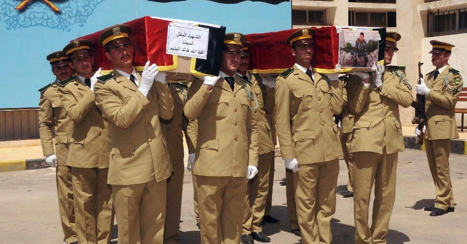 23.mai.2012 - Fotografia divulgada pela agência síria de notícias, a Sana, mostra forças de segurança levando caixões de ex-companheiros, durante funeral em hospital militar em Damasco, capital da Síria