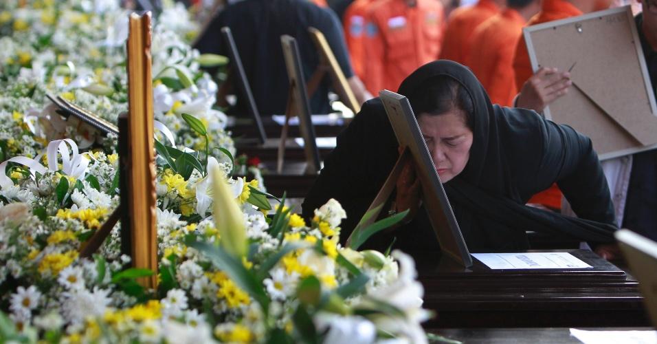 23.mai.2012 - Mulher beija fotografia de vítima de acidente com avião Sukhoi no aeroporto Halim Perdanakusuma, em Jacarta, na Indonésia