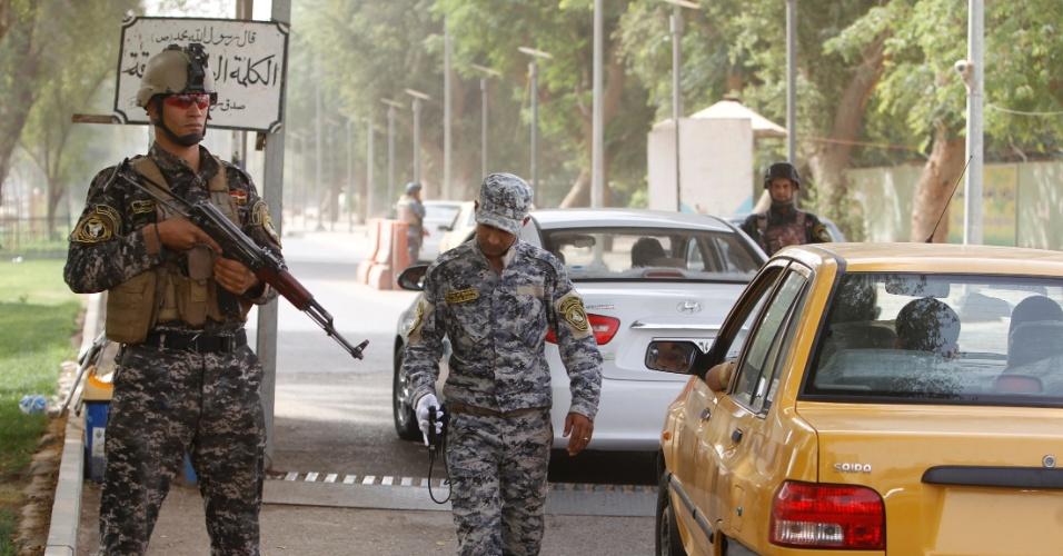 23.mai.2012 - Policiais realizam blitz em rua de Bagdá, no Iraque
